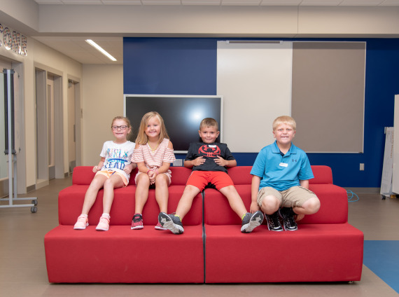 kids smiling at school on a couch - adams central elementary school hastings nebraska